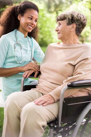 Gehandicapte vrouw en zorgzame arts in de tuin