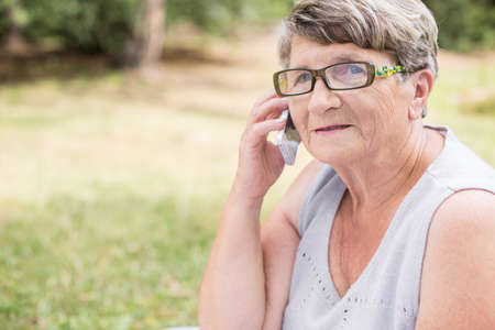 aged: Image of elderly woman in park talking on mobilephone