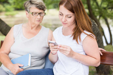 intergenerational: Image of intergenerational relation between two women relaxing in park Stock Photo