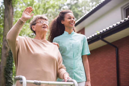 old people in care: Nurse walking with patient in front of rest home