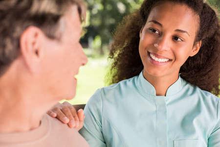helper: Senior woman talking with African American nurse Stock Photo