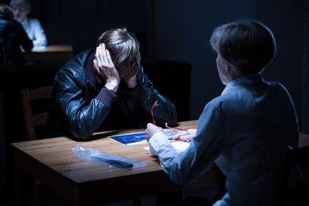 investigación: Delincuente joven que cubre las orejas durante el interrogatorio policial Foto de archivo