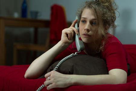 mujer en la cama: Muchacha triste con problemas de hablar por teléfono Foto de archivo