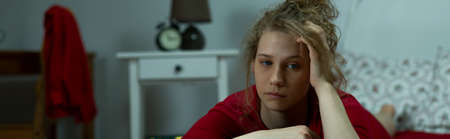 exasperated: Exasperated young woman lying on the bed