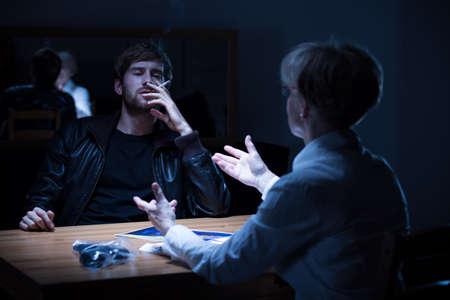 interrogating: Suspected man smoking a cigarette during police interrogation