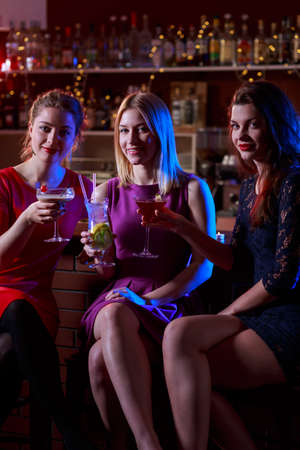 cocktail bar: Three attractive female friends sitting in cocktail bar