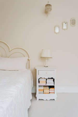 bedstead: Bedside table with shelves for books in bedroom Stock Photo