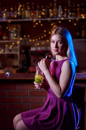 pretty dress: Young pretty woman with drink sitting at bar Stock Photo