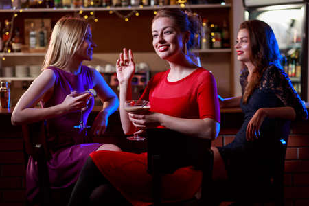cocktail bar: Attractive brunette with two pretty friends in cocktail bar