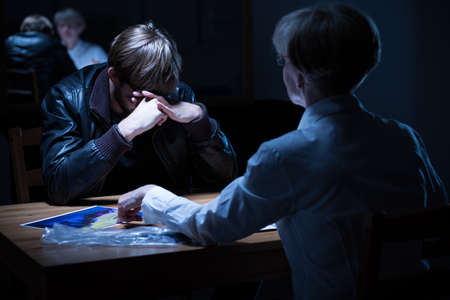 constabulary: Young crying criminal in police interrogation room