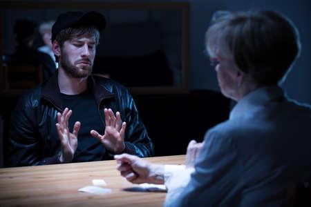 Hombre del drogadicto interrogado por policía en una habitación oscura Foto de archivo