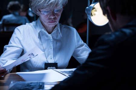 femme policier: Image de aînée policière examinant un homme soupçonné Banque d'images