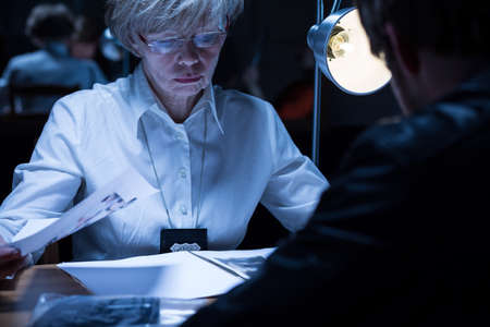 delinquent: Image of elder policewoman examining a suspected man