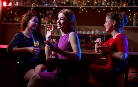 drinks on bar: Three beautiful young woman sitting at bar with drinks