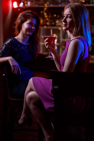 women legs: Photo of two young women sitting at bar Stock Photo