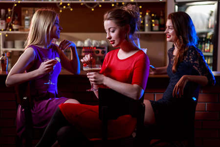 bars: Image of three beautiful friends sitting in cocktail bar