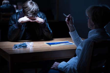 mujer policia: Mujer policía fumando un cigarrillo durante el interrogatorio penal Foto de archivo
