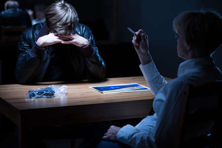 Policewoman smoking a cigarette during criminal interrogation Stock Photo