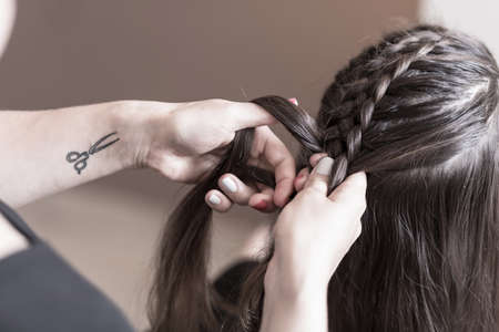 plait: Hairdresser making a braid on long hair