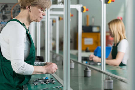 assembly line: Senior woman is working on assembly line