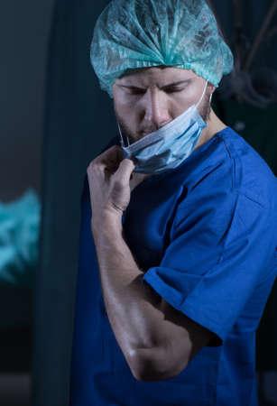 cansancio: Cirujano joven después de la operación en el hospital