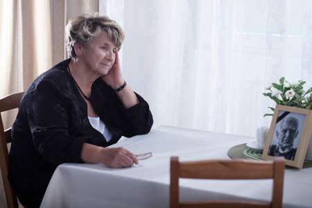Senior woman looking at dead husband's picture Stockfoto