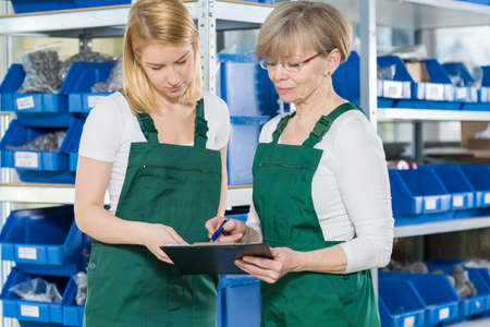 focus: Blue-collar female workers are in the warehouse Stock Photo