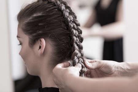 美しい結婚式のヘアスタイルを行う美容師のクローズ アップ