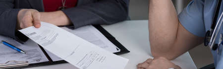 a medical examination: Close-up of head of hospital ward needs her employee to sign documents
