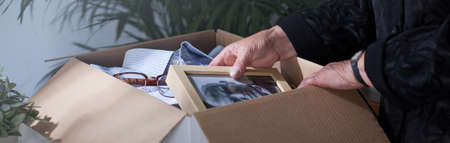'hide out': Woman packing dead husbands photography to moving box Stock Photo