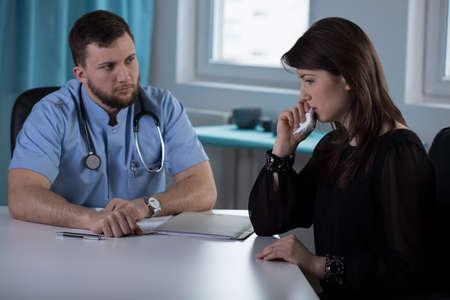 젊은 의사가 나쁜 소식을 그 여인에게 전해주어야합니다. 스톡 콘텐츠