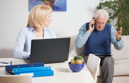 angry: Elderly irate man talking phone with the client Stock Photo