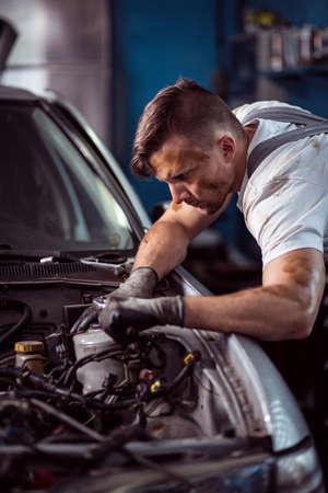servicing: Portrait of young handsome man servicing car in workshop