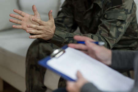 Soldier sitting on the sofa during psychological therapy Stockfoto