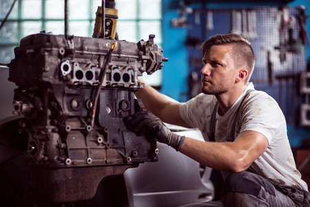 motors: Photo of uniformed car technician maintaining automotive engine Stock Photo