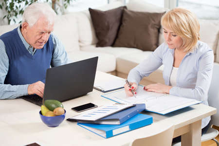 work from home: Photo of two elderly people having work at home