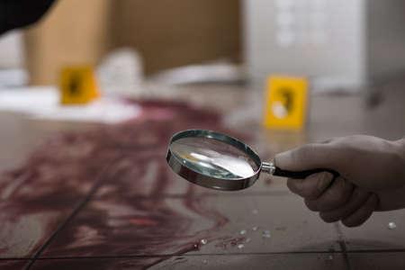 Científico forense en busca de sangre a través de la lupa
