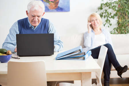 transact: Senior businessman focused on work at home