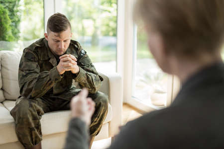 Image of depressed military man visiting psychologist