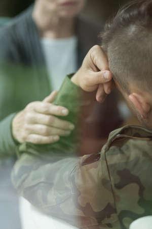 psychiatrist: Mature female psychiatrist comforting soldier with depression