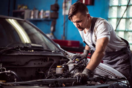 Photo of handsome worker of service station repairing vehicle
