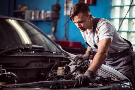 Foto von handsome Arbeitnehmer der Tankstelle Reparatur Fahrzeug Standard-Bild - 43943420