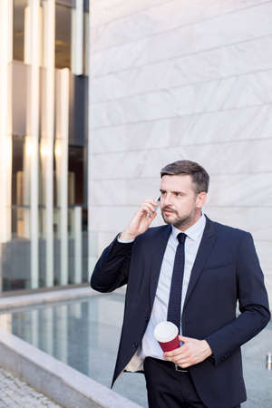 worker working: Image of confident financial worker in suit working outdoor Stock Photo