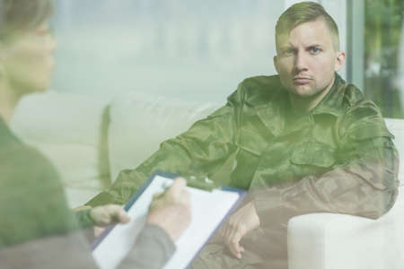 counseling session: Troubled soldier during psychotherapy session at psychiatrists office