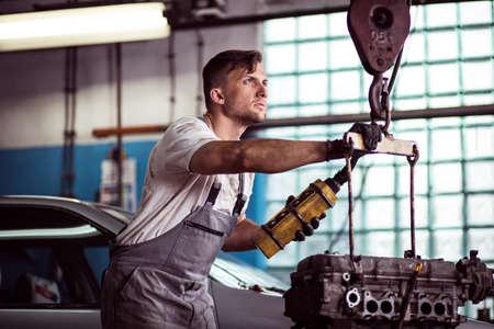 hoist: Image of auto workshop worker using engine hoist