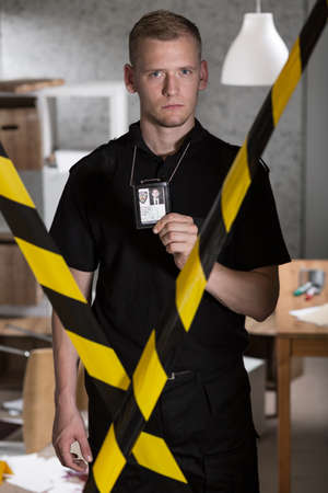 constabulary: Policeman standing behind warning tape and showing police badge Stock Photo