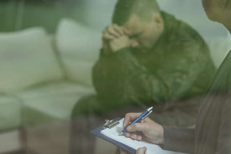 therapy room: Depressed glum soldier during therapy of depression