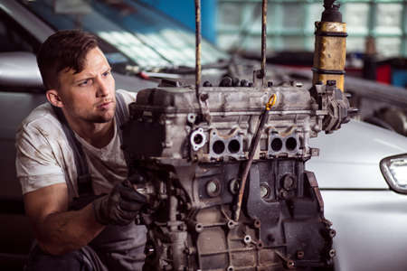Photo of professional auto technican diagnosing engine problem