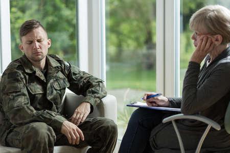 enfermedades mentales: Mature psychologist talking with despair young soldier Foto de archivo