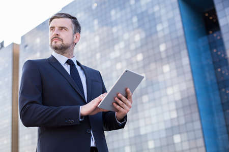 office use: Image of handsome economic trade worker standing outdoor Stock Photo